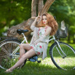 Beautiful girl wearing a nice short dress having fun in park with bicycle. Pretty red hair woman with romantic look posing sitting on her bike in a sunny day. Gorgeous curly redhead relaxing outdoor. — Stock Photo