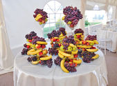Fruits arrangement on restaurant table. Wedding decoration with fruits, bananas, grapes and apples. — Stock Photo