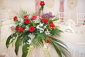 Beautiful wedding arrangement on restaurant table. Elegant wedding arrangement. Luxury restaurant hall dressed up for wedding reception. — Стоковое фото