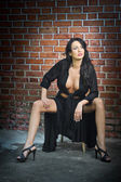 Charming young brunette woman in black and high heels near the brick wall. Sexy gorgeous young woman near old wall. Full length portrait of a provocative woman with long hair near a brick wall — Foto de Stock