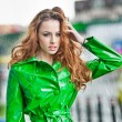 Beautiful woman in bright green coat posing in the rain. Dramatic redhead staying in the rain drops, urban shot. Attractive red hair girl on the street in a rainy day. Emotional pretty young female. — Stock Photo #48803925