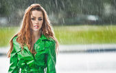 Beautiful woman in bright green coat posing in the rain. Dramatic redhead staying in the rain drops, urban shot. Attractive red hair girl on the street in a rainy day. Emotional pretty young female. — Foto de Stock