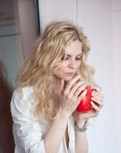 Portrait of a young, blond woman, holding a mug with both her hands, wearing a white shirt and black pants, with an expression of being sadness. Woman posing with a big red cup of tea in her hands. — Stock Photo