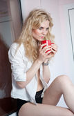 Portrait of a young, blond woman, holding a mug with both her hands, wearing a white shirt and black pants, with an expression of being sadness. Woman posing with a big red cup of tea in her hands. — Photo