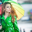 Beautiful woman in bright green coat posing in the rain holding a multicolored umbrella. Dramatic redhead staying under umbrella, urban shot. Attractive red hair girl on the street in a rainy day. — Stock Photo