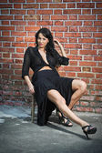Charming young brunette woman in black and high heels near the brick wall. Sexy gorgeous young woman near old wall. Full length portrait of a provocative woman with long hair near a brick wall — Stock Photo