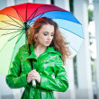 Beautiful woman in bright green coat posing in the rain holding a multicolored umbrella. Dramatic redhead staying under umbrella, urban shot. Attractive red hair girl on the street in a rainy day. — Stock Photo #49337485