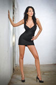 Charming young brunette woman in black tight fit dress posing against a wall. Sexy gorgeous young woman with high heels. Full length portrait of a provocative woman with long hair and sporty allure — Stock Photo
