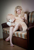 Young blond sensual woman sitting on sofa relaxing with a huge teddy bear. Beautiful girl with comfortable clothes relaxing on the couch with a toy. Attractive blonde in cosy scenery indoor — Stok fotoğraf