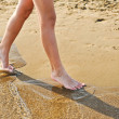 Beach travel - young girl walking on sand beach leaving footprints in the sand. Closeup detail of female feet and golden sand. Teenage female,walking down the beach. Nice legs walking near water — Stock Photo #50411121