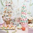 Wedding decoration with pastel colored cupcakes, meringues, muffins and macarons. Elegant and luxurious event arrangement with colorful macaroons. Wedding dessert with macaroons — Stock Photo #50537777