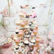 Wedding decoration with pastel colored cupcakes, meringues, muffins and macarons. Elegant and luxurious event arrangement with colorful macaroons. Wedding dessert with macaroons — Stock Photo #50537791
