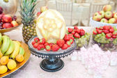 Fruits arrangement. Fresh various fruits elegant decoration. Assortment of exotic fruits. Multicolored fruits. Wedding decoration with fruits on restaurant table, pineapple, bananas, nectarines, kiwi — Stock Photo
