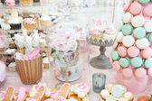 Wedding decoration with pastel colored cupcakes, meringues, muffins and macarons. Elegant and luxurious event arrangement with colorful macaroons. Wedding dessert with macaroons — Stockfoto