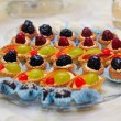 Set of tasty mini cakes with raspberries, blackberries, cranberries, blueberries and grapes on white table. Wedding decoration with mini tarts with various berries. Arrangement with mini tarts. — Stock Photo #50586333