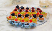 Set of tasty mini cakes with raspberries, blackberries, cranberries, blueberries and grapes on white table. Wedding decoration with mini tarts with various berries. Arrangement with mini tarts. — Stock Photo