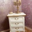 Golden candlestick with five candles on white wooden furniture in front of luxurious textured wall. Vintage candelabra, candles and golden boxy on classic dresser with wallpaper as background — ストック写真 #50887641