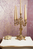 Golden candlestick with five candles on white table, in front of luxurious textured wall. Vintage candelabra, candles and golden boxy on table with wallpaper as background — Stock Photo