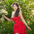 Young voluptuous brunette holding a wild flowers bouquet in a sunny day. Portrait of beautiful woman with low-cut red dress smiling, outdoor shot. Provocative female in short dress enjoying the nature — Stock Photo #50946229