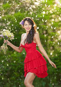 Young voluptuous brunette holding a wild flowers bouquet in a sunny day. Portrait of beautiful woman with low-cut red dress smiling, outdoor shot. Provocative female in short dress enjoying the nature — Stock Photo