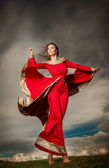 Fashionable beautiful young woman in red long dress posing outdoor with cloudy dramatic sky in background. Attractive long hair brunette girl with elegant luxurious dress on stormy sky. — Stock Photo