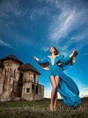 Modne piękna młoda kobieta w niebieska suknia z starego zamku i słabe dramatyczne niebo w tle. atrakcyjny brunetka dziewczynka z elegancka sukienka luksusowe, na zewnątrz strzał. — Zdjęcie stockowe