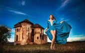 Fashionable beautiful young woman in long blue dress posing with old castle and cloudy dramatic sky in background. Attractive long hair brunette girl with elegant luxurious dress, outdoors shot. — Zdjęcie stockowe