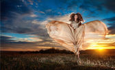 Fashionable beautiful young woman in nude colored long dress spinning around looking as a butterfly on cloudy dramatic sky in sunset. Attractive brunette with elegant luxurious dress, outdoors shot. — Stock Photo