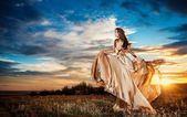 Fashionable beautiful young woman in nude colored long dress leaving, cloudy dramatic sky in background. Attractive long hair brunette girl with elegant luxurious dress, outdoors shot. — Stock Photo