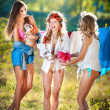 Three sexy women with provocative outfits putting clothes to dry in sun. Sensual young females laughing putting out the washing to dry in sunny day. Perfect body housewives with a dog, shot in forest — Stock Photo #51022663