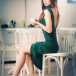 Fashionable attractive young woman in green dress sitting in restaurant. Beautiful redhead posing in elegant scenery with a cup of coffee in her hand. Pretty female on high heels drinking coffee. — Stock Photo #51059397