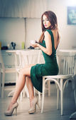 Fashionable attractive young woman in green dress sitting in restaurant. Beautiful redhead posing in elegant scenery with a cup of coffee in her hand. Pretty female on high heels drinking coffee. — Stock Photo