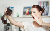 Beautiful, smiling red hair woman taking photos of herself with a camera. Fashionable attractive female taking a self portrait. Selfie, indoor, horizontal. Beautiful redhead taking pictures of herself — Stock Photo