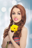 Portrait of beautiful girl in studio with yellow chrysanthemum in her hands. Sexy young woman with blue eyes with bright flowers. Redhead, creative hairstyle and makeup, fashion photo studio shot — Stock Photo