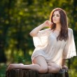 Young beautiful red hair woman wearing a transparent white blouse posing on a stump in a green forest. Fashionable sexy attractive girl sitting on hub in sunny day. Gorgeous redhead in garden. — Stock Photo #51121587