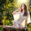 Young beautiful red hair woman wearing a transparent white blouse posing on a stump in a green forest. Fashionable sexy attractive girl sitting on hub in sunny day. Gorgeous redhead in garden. — Stock Photo #51121601