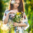 Young beautiful red hair woman holding a wild flowers bouquet in a sunny day. Portrait of attractive long hair female with flowers in hair, outdoor shot. Pretty girl enjoying the nature in summer — Stock Photo #51121607