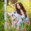 Young beautiful red hair woman in multicolored blouse in a sunny day. Portrait of attractive long hair female in the middle of wild flowers, outdoor shot. Pretty girl enjoying the nature in summer — Stock Photo #51121615