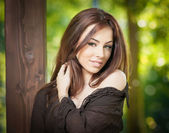 Beautiful female portrait with long brown hair outdoor. Genuine natural brunette with long hair in park. Portrait of a attractive woman with beautiful eyes and black blouse near a tree — Stock Photo