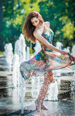 Attractive girl in multicolored short dress playing with water in a summer hottest day. Girl with wet dress enjoying fountains. Young beautiful happy female playing with outdoor water fountains. — Stock Photo