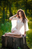 Young beautiful red hair woman wearing a transparent white blouse posing on a stump in a green forest. Fashionable sexy attractive girl sitting on hub in sunny day. Gorgeous redhead in garden. — Stock Photo