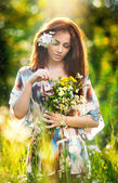 Young beautiful red hair woman holding a wild flowers bouquet in a sunny day. Portrait of attractive long hair female with flowers in hair, outdoor shot. Pretty girl enjoying the nature in summer — Stock Photo