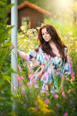 Young beautiful red hair woman in multicolored blouse in a sunny day. Portrait of attractive long hair female in the middle of wild flowers, outdoor shot. Pretty girl enjoying the nature in summer — Stock Photo