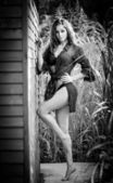 Fashion portrait of sexy brunette in black swimsuit leaning on wooden cabin wall. Sensual attractive woman with long legs, black and white shot. Perfect body girl with long hair posing provocatively — Stock Photo