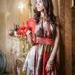Young beautiful brunette woman in elegant multicolored dress standing near a large wall mirror. Sensual romantic lady holding a red fan in luxurious vintage interior, daydreaming. Pretty girl with fan — Stock Photo #51254981