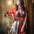 Young beautiful brunette woman in elegant multicolored dress standing near a large wall mirror. Sensual romantic lady holding a red fan in luxurious vintage interior, daydreaming. Pretty girl with fan — Stock Photo #51254989