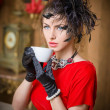 Fashionable attractive young woman in red dress drinking coffee in restaurant. Beautiful brunette in elegant vintage scenery holding a cup of coffee. Attractive lady with gloves and creative hairstyle — Stock Photo