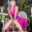 Fashionable attractive young woman in pink dress sitting in restaurant, beyond the window. Beautiful female posing in elegant vintage scenery with a lemonade. Photo concept through the window — Stock Photo #51255017