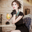 Fashionable attractive young woman in black dress sitting in restaurant. Beautiful brunette posing in elegant vintage scenery with a juice glass. Attractive lady with gloves in luxurious interior — Stock Photo #51255187
