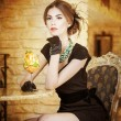 Fashionable attractive young woman in black dress sitting in restaurant. Beautiful brunette posing in elegant vintage scenery with a juice glass. Attractive lady with gloves in luxurious interior — Stock Photo
